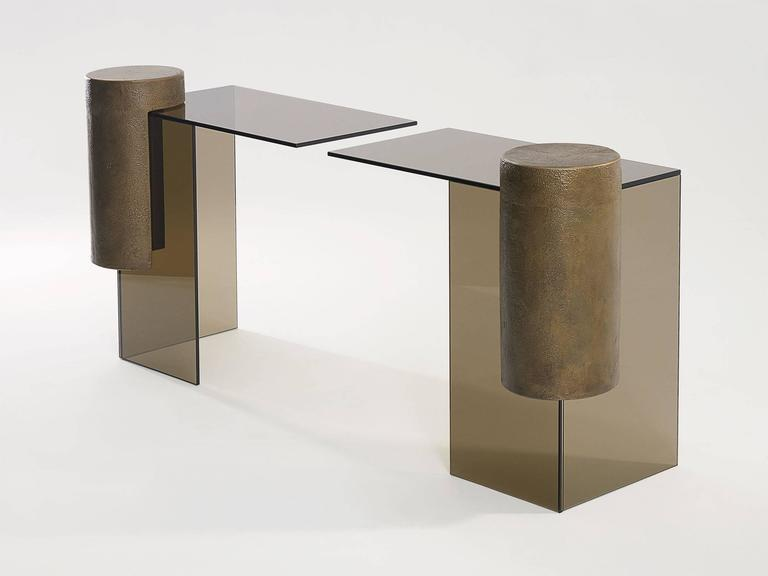 Smoked glass and brass console table comprised of two separate tables reaching towards each other by Los Angeles designer Brian Thoreen. Cantilevered by a brass column, the glass elements reach towards each other to create the table surface.
