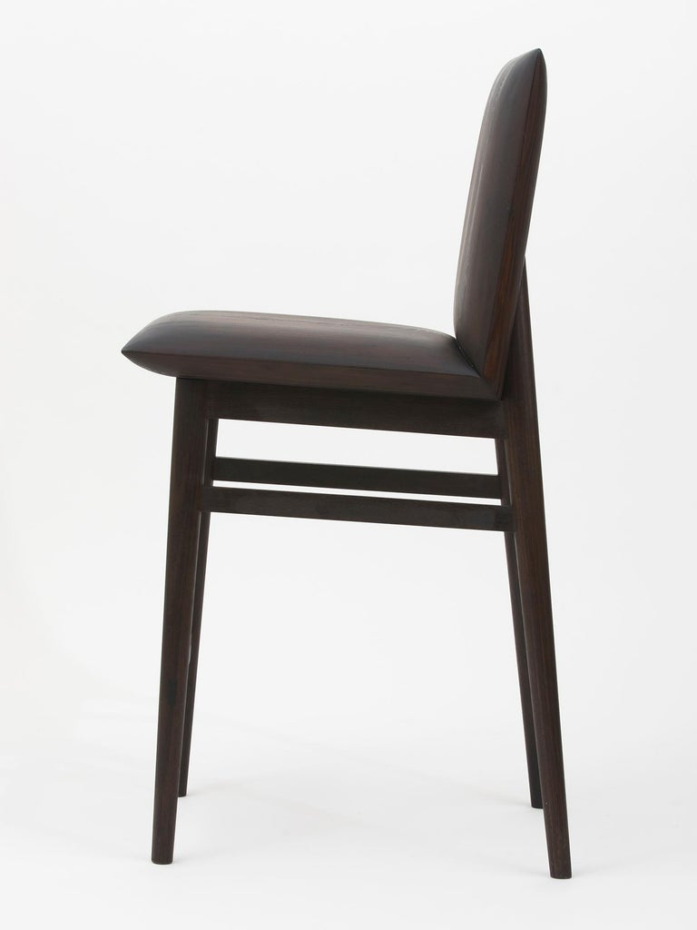 Ebonized redwood, walnut and brass bar stool or counter stool with brass reinforced footrest and beautiful curved seat and back. The hand-carved seat gives the illusion of upholstery, but is solid and durable! Handmade by Hudson Valley-based artist