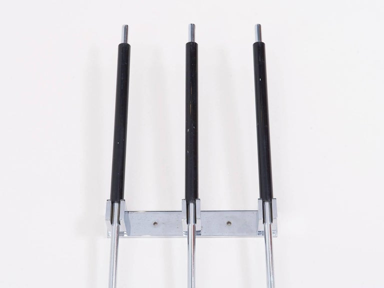 Unusual three-piece set of chrome-plated fireplace tools that hang on the wall, made by the Italian company Albrizi in the 1960s. Consists of a brush, poker and shovel with black lacquered handles and a chrome a wall mount.