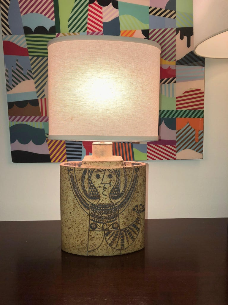 Elliptical table lamp has a rough ceramic texture with a decorative figure of a female on the front. On the lower back is an etched signature that reads