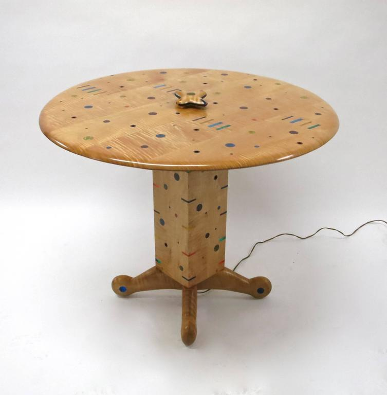 Dining or center table in excellent condition by Daniel Peters commissioned in mid 90's and completed in 1999 for the previous owner. The table is made of curly maple wood with colored acrylic accents in shapes of full circles, hollow circles, and