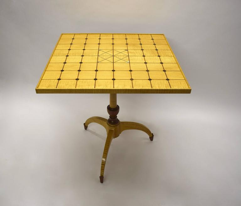 Single commissioned, handmade table in excellent condition made and signed by Dale Broholm in Bubinga and Ebony woods. The square top has intersecting perpendicular lines with round, inlaid Ebony details and four triangular details in Abalone. The