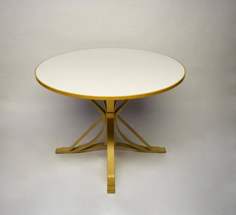 """""""Face-Off"""" dining table with a white laminate top and maple base. Around the table are four """"Hat-Trick"""" side chairs also in maple wood. The set was fabricated in 1997 by Knoll and has its original tags and stampings."""