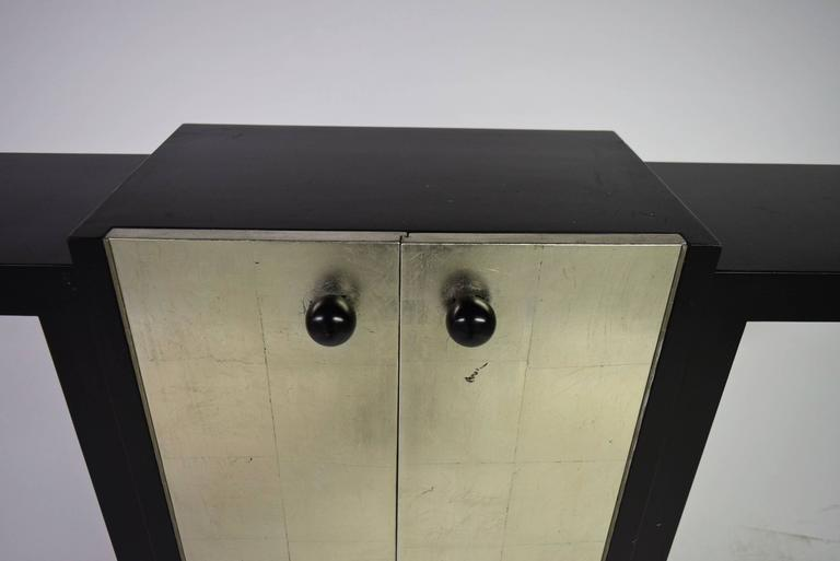French Deco Console in black lacquer has a centre cabinet with two doors in silver leaf.