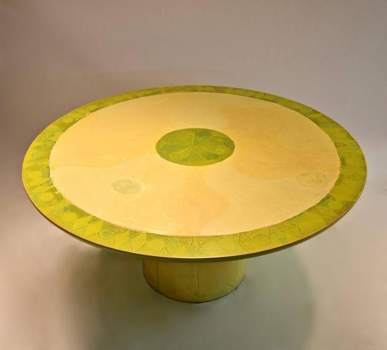 Unique, commissioned dining center table by artist and designer Randy Shull with a round, beveled top and a cylindrical base that has eight round plastic protective feet. The table is done in layered, sanded, hand painted wood in tones of green and