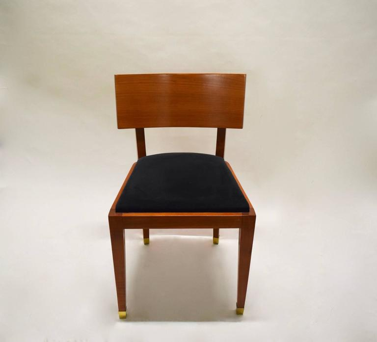 Four armless dining chairs in fruitwood with a curved backrest, tapered legs, solid brass sabots, and the seat cushion upholstered in black micro suede that was recovered in the early 2000s. The dining table is also available.