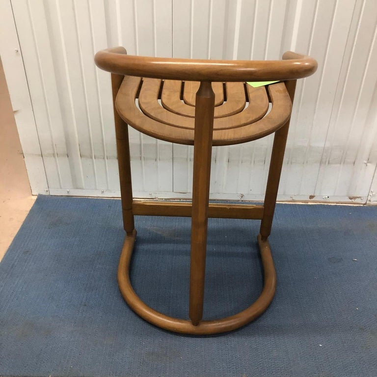 A set of three handsome midcentury bar stools in medium colored wood. Measures: 32