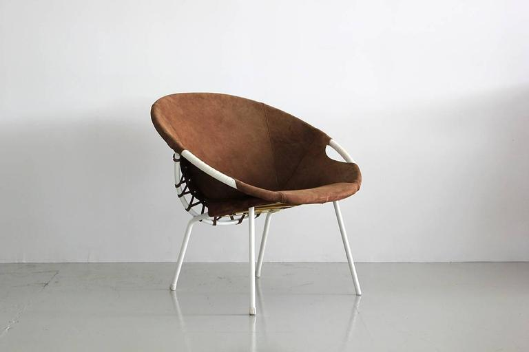 Austrian white iron and brown suede scoop chair with whip stitch detail.