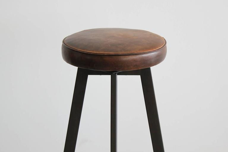 """Great newly produced Iron """"T"""" barstool by Orange Los Angeles. Simple iron design with floating T footrest. Newly upholstered brown leather swivel seat.  Seat measures 14"""" diameter."""