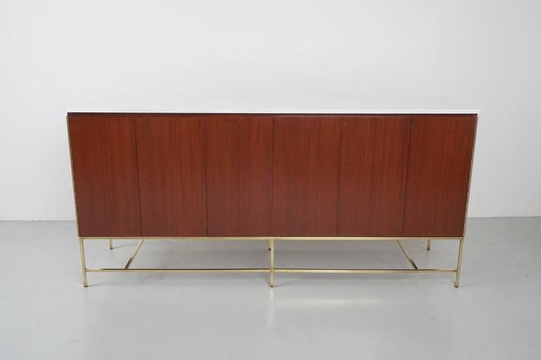 Gorgeous Paul McCobb credenza for Calvin featuring two bi-folding doors with ample storage on both sides consisting of four drawers and storage. Signed with original manufacturer's label. Beautiful original solid milk glass piece top and newly