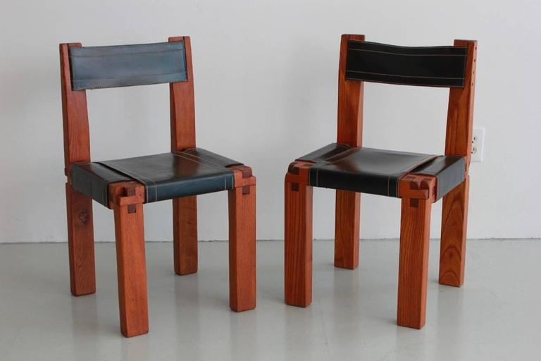 Pair of chairs designed by French designer Pierre Chapo for Atelier Chapo, Paris. Cubic design of solid elmwood with black leather seat. Beautiful wood joint detail and fantastic patina to leather with contrast stitching. Priced as a pair.