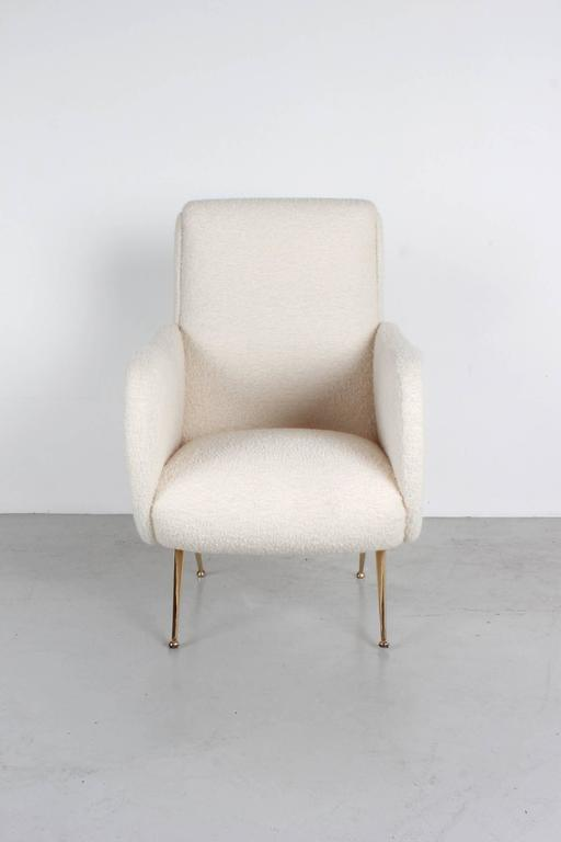 Pair of Italian club chairs in the style of Marco Zanuso upholstered in creamy white bouclé with newly polished brass tapered legs.