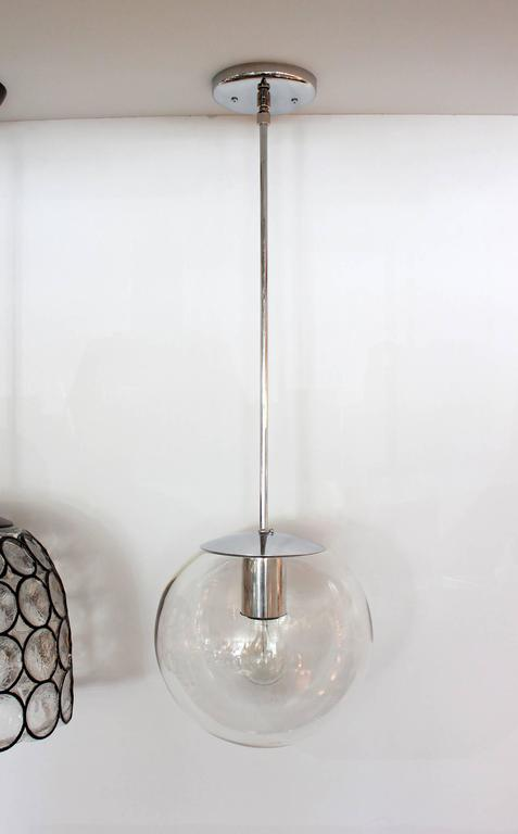 Clear hand blown glass globe with nickel hardware and canopy. Newly rewired. Two available. Priced individually.