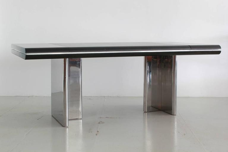 Gorgeous black mahogany and leather executive desk by Hans Von Klier for Skipper. Massive surface with three small pull-out drawers. Desk has large inset black leather blotter on surface and rests on solid stainless steel legs. Newly refinished.