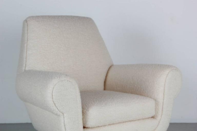 Fantastic Italian club chairs designed by Gigi Radici upholstered in a creamy white bouclé with polished brass legs.