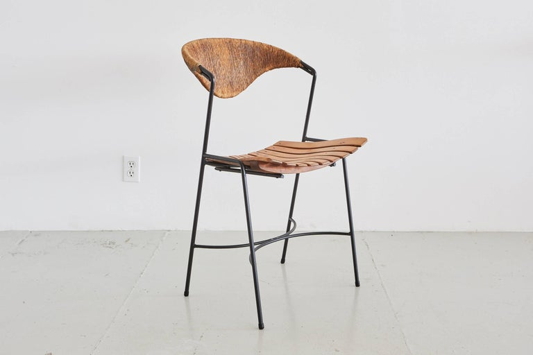 Simple side chair by Arthur Umanoff. Iron frame with slatted seat and signature rushed back.