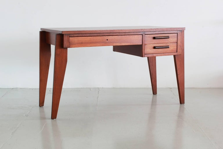 Wonderful desk by French designer Andre Sornay. Warm French oak with contrasting wood handles on two drawers and pencil centre drawer. Prouve style angled legs. Fantastic piece!