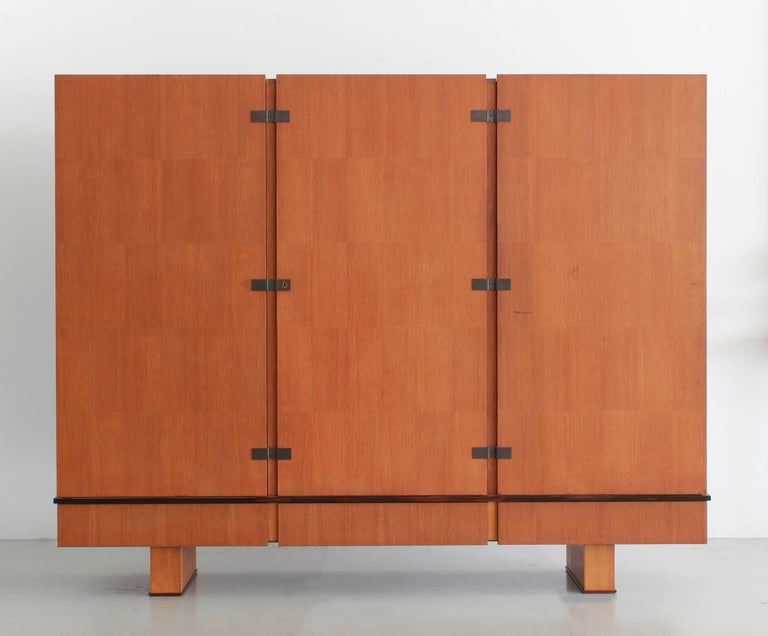 Large-scale three-door wardrobe and cabinet opening in front by three locking doors (side doors have keyholes on side of cabinet) and three lower pull out drawers. Well restored to capture original integrity of piece, circa 1950.  Middle cabinet