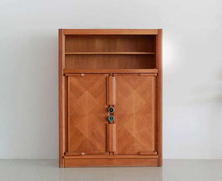 Incredible cabinet by Robert Guillerme (1913-1990) and Jacques Chambron (1914-2001) with an open display shelf and interior shelving enclosed by oak doors in geometric grain pattern and signature ceramic hardware. 