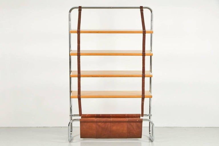Impressive large-scale Italian wall shelf designed by Luigi Massoni for Poltrona Frau, 1971. Chromed tubular steel frame with natural wood shelves suspended by brown leather straps. Gorgeous brown saddle leather catch all at base - perfect for