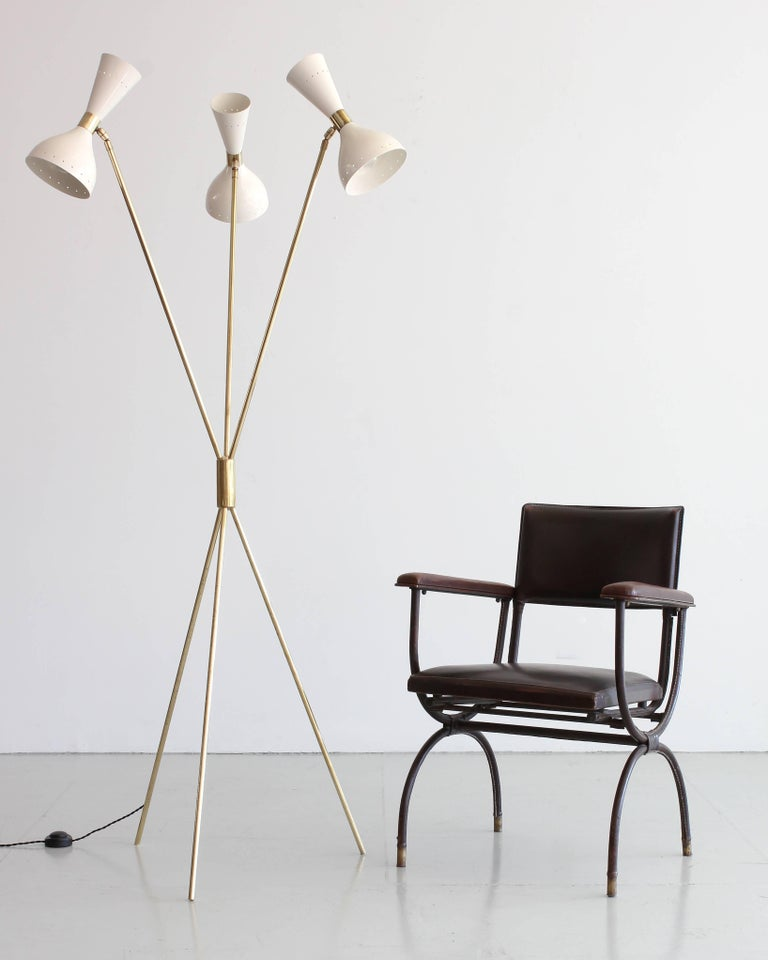 Fantastic tripod floor lamp attributed to Stilnovo with three articulating creamy white shades, brass arms and base. Newly rewired.