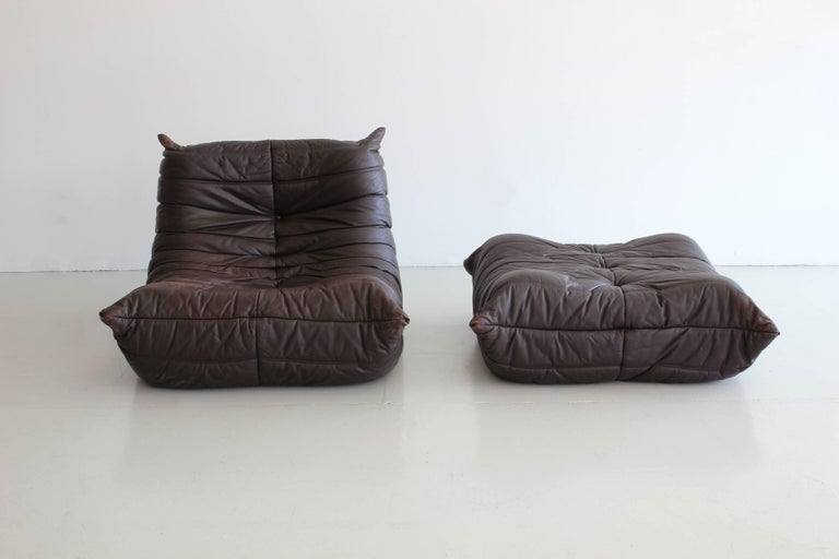 """Pair of """"Togo"""" lounge chairs and matching ottoman from Ligne Roset designed by Michel Ducaroy. Original dark chocolate leather with wonderful patina.   Lounge chair: H 70, W 87, D 102 cm Pouf H 30, W 87, D 95."""