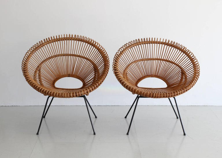 Beautiful rattan bucket chairs in the style of Franco Albini. Wonderful shape with small open back makes for an airy and aesthetically pleasing design. Great looping rattan detailing around edges. Black iron base. Very comfortable and artistic