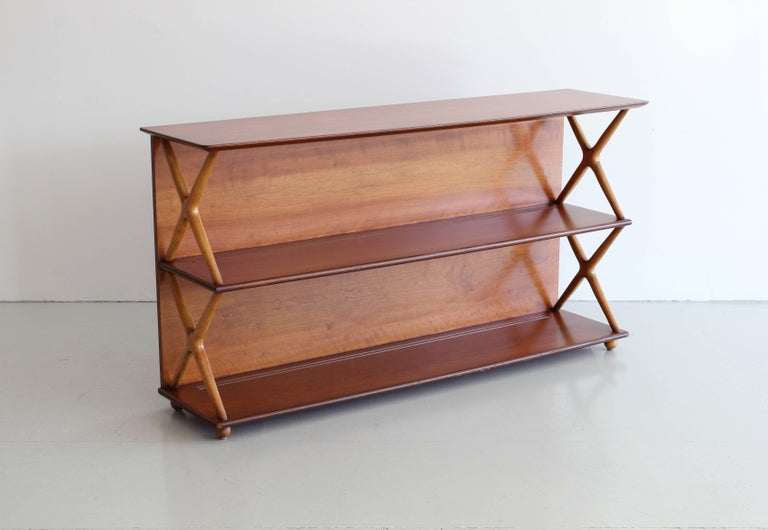 Renzo Rutili bookcase for Johnson Furniture. Simple mahogany bookshelf with crosses sides in a slightly lighter color.