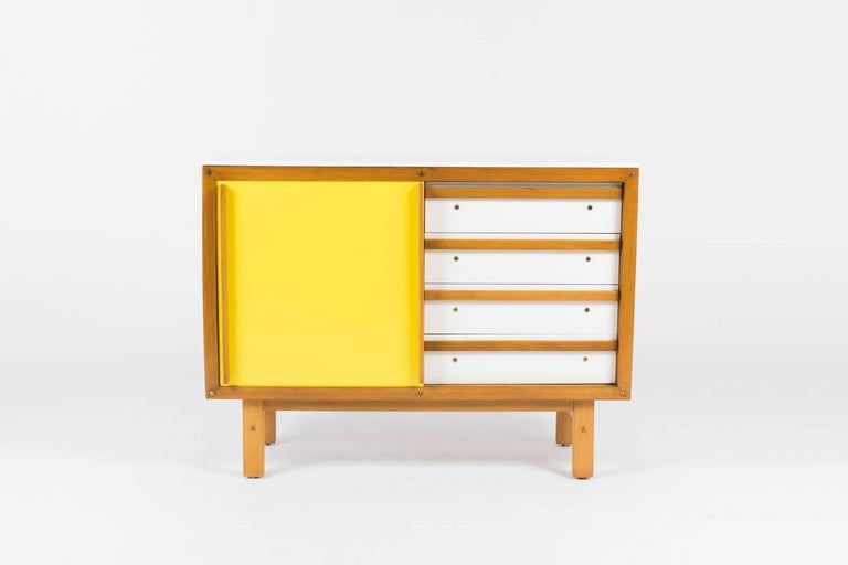 Rare dresser cabinet by French cabinetmaker Andre Sornay. Cabinet has pop of color yellow and oak with sliding door revealing drawers on one side and open shelving on the other.
