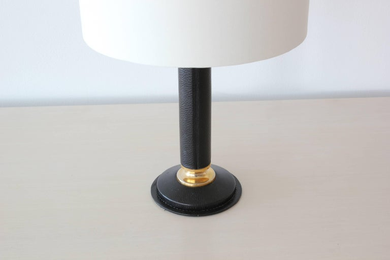 Handsome French black leather table lamp in the style of Jacques Adnet with brass accents.  Newly rewired and new silk shade with gold lining.