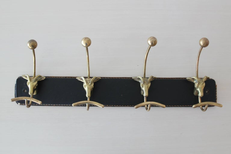Coat rack attributed to Jacques Adnet with brass shaped rams heads.