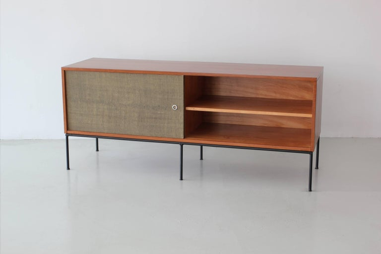 Paul McCobb credenza with sliding caned doors and open shelving on black iron base. 