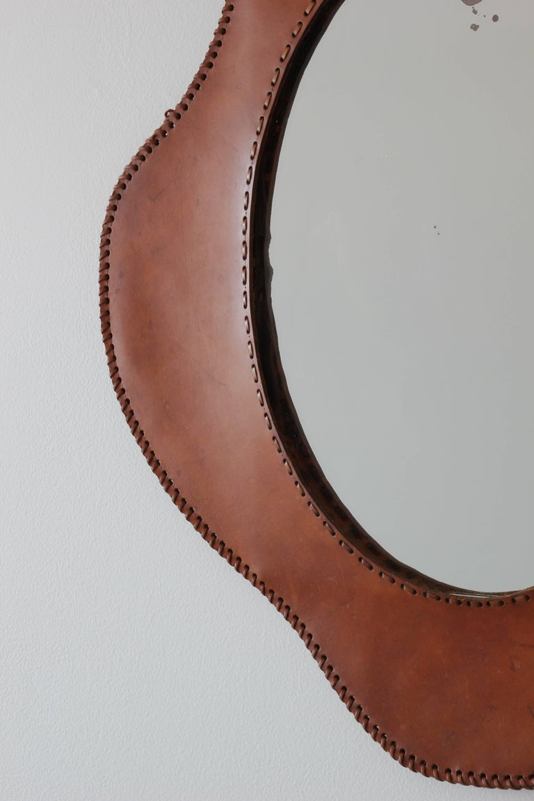 Sculptural French leather mirror in the style of Jacques Adnet with undulating curves and contrast stitching. Wonderful patina to saddle leather.