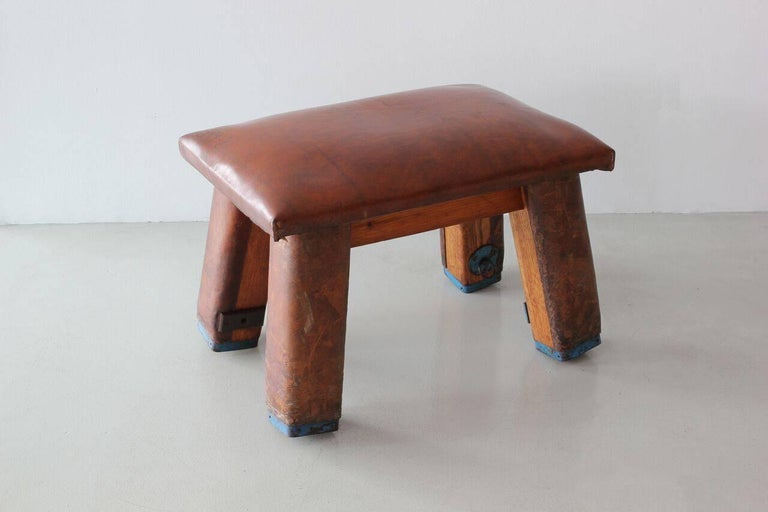 1920s antique gym bench, French. Lots of patina, imperfections, blue painted feet, numbers written on leather and overall charm!