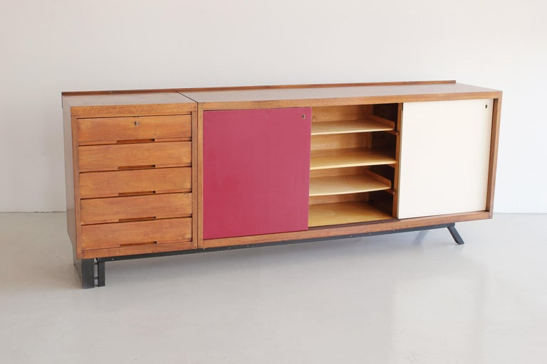 Incredible Italian sideboard in the style of Charlotte Perriand with wood drawers, sliding doors and iron asymmetrical base.