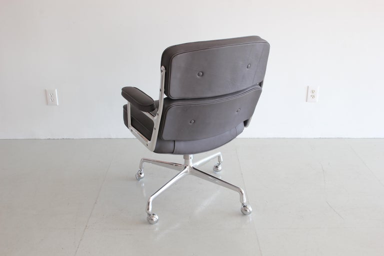 Classic office chair from the Time Life building in New York. Designed by Eames featuring newly upholstered in grey leather, new casters and a newly polished aluminum base and frame. Chair is height adjustable with tilt and swivel.