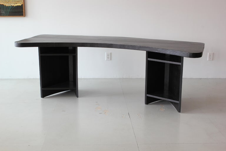 Unique boomerang shaped desk with open grain oak stained with charred black finish. 1950s French school in period of Pierre Chapo. Triangular shaped open alcoves. Beautiful finish with textured top and unique elliptical shape.