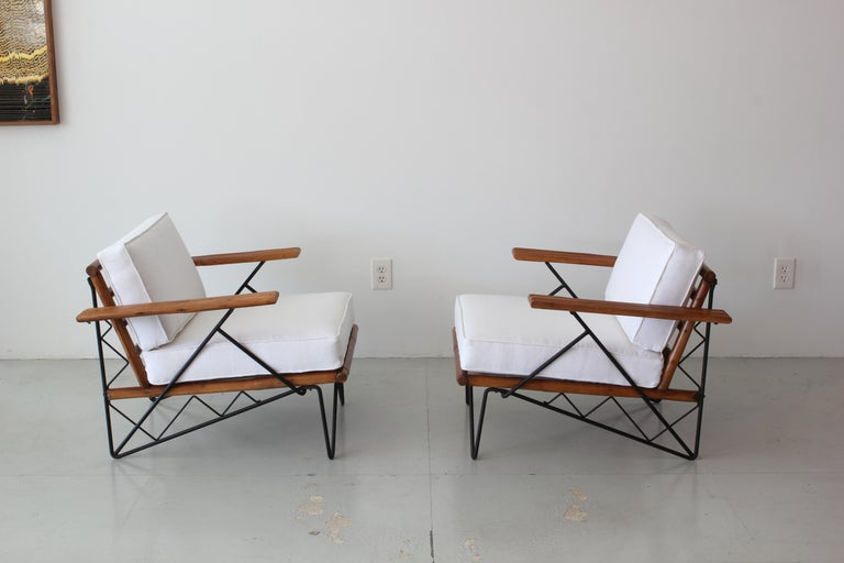 Pair of chairs from Ritts Furniture company, circa 1960s. Interesting iron base Rattan arms and slatted back Newly uphostered in white linen.