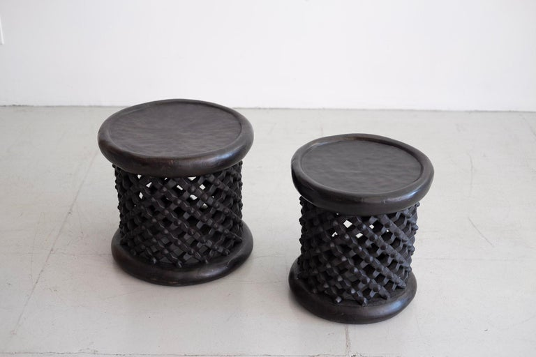 Two African Bamileke spider stools or tables in ebonized wood with intricate carved lattice detailing. Sold and priced individually.   Measures: Large - 17