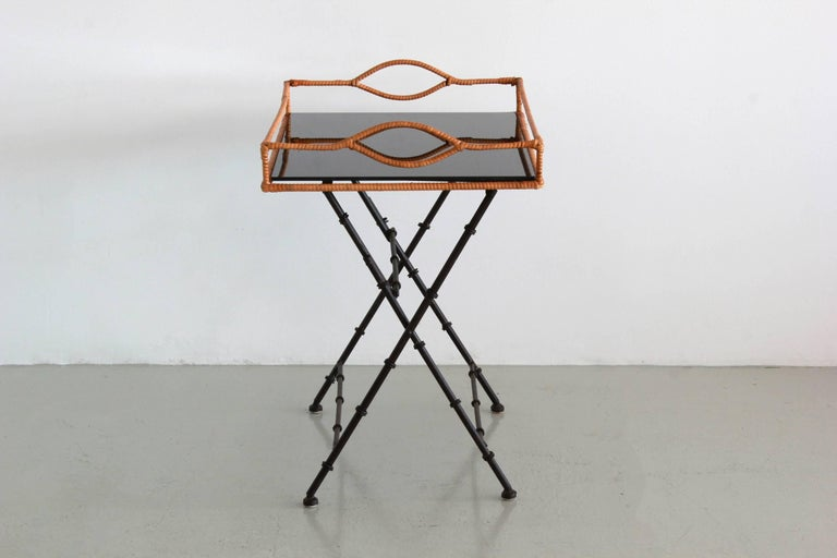 Handsome Jacques Adnet style tray table with bamboo iron legs, rattan wrapped tray with black mirror tray.