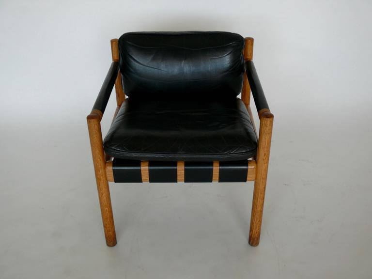Pair of oak and leather armchairs attributed to Carlo Scarpa. Beautiful patina to black leather and oak with straps supporting seat cushions.