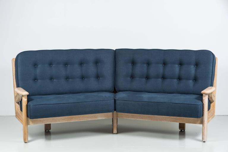 Fantastic French settee by Guillerme et Chambron refinished in a newly refinished cerused oak. Comfortable cushions newly upholstered in navy blue linen with button-tufted back. Gorgeous geometric wood detailing from the back and would look great
