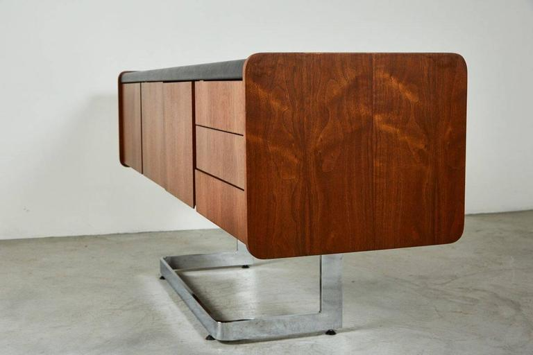 Ste-Marie and Laurent credenza with black inset leather top, one deep file drawer on one side, three pencil drawers on the right side, flanking two center doors opening into a cabinet for storage.