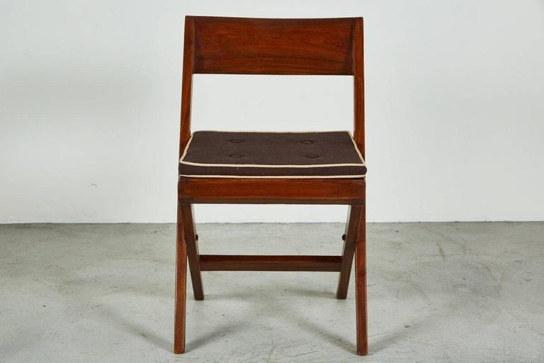 Pierre Jeanneret library chair designed for the Panjab University Library in the city of Chandigarh, India. The chair is made out of solid teak and cane with original cushion seat.