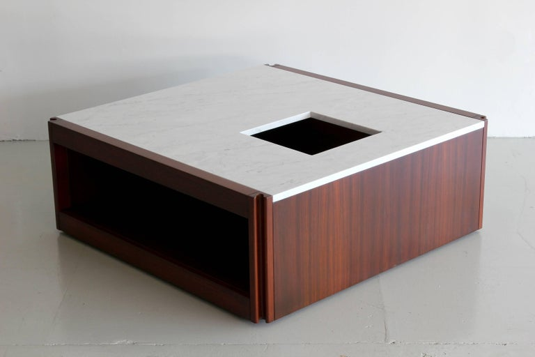 Rare marble and rosewood coffee table by Angelo Mangiarotti for Molteni. Beautiful squared shape with rosewood base and marble top with two cubby hole openings and a central plant holder. The piece has all edges designed with an ergonomic shape and