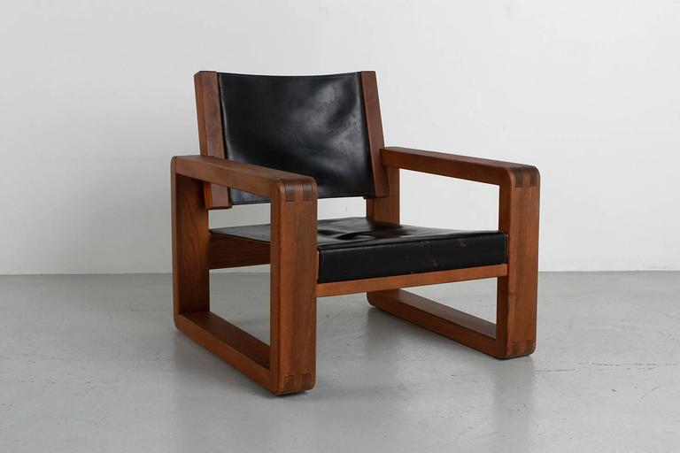 Armchair designed in the style of French designer Pierre Chapo for Atelier Chapo, Paris. Cubic design of solid elmwood with black leather seat. Beautiful wood joint detail and fantastic patina to leather with contrast stitching. Great scale.