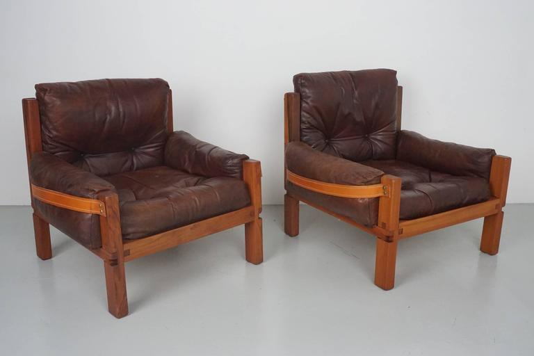Fantastic pair of leather club chairs designed by French designer Pierre Chapo for Atelier Chapo, Paris. Cubic design of solid Elmwood with chocolate leather seat and contrasting leather strap wraps behind seat and sides. Beautiful wood joint detail