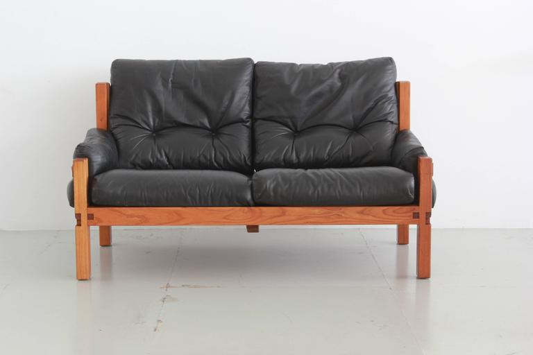 Two-seat sofa by Pierre Chapo. Solid elm and black leather with contrasting cognac leather side straps.