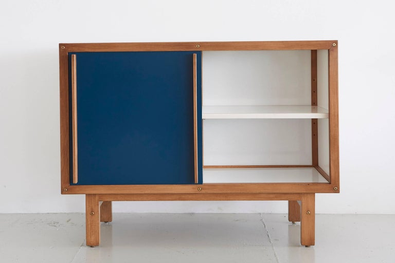 Andre Sornay sideboard with white drawers on one side and open shelving on the other with blue sliding door.