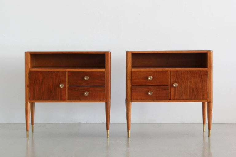 Exquisite pair of Paolo Buffa nightstands from Italy.  Beautifully refinished mahogany wood with open shelf, two small drawers and open door storage on both.  Original glass tops with brass hardware and tapered legs with brass feet.  Great